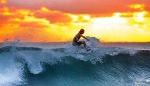 guy surfing at sunrise