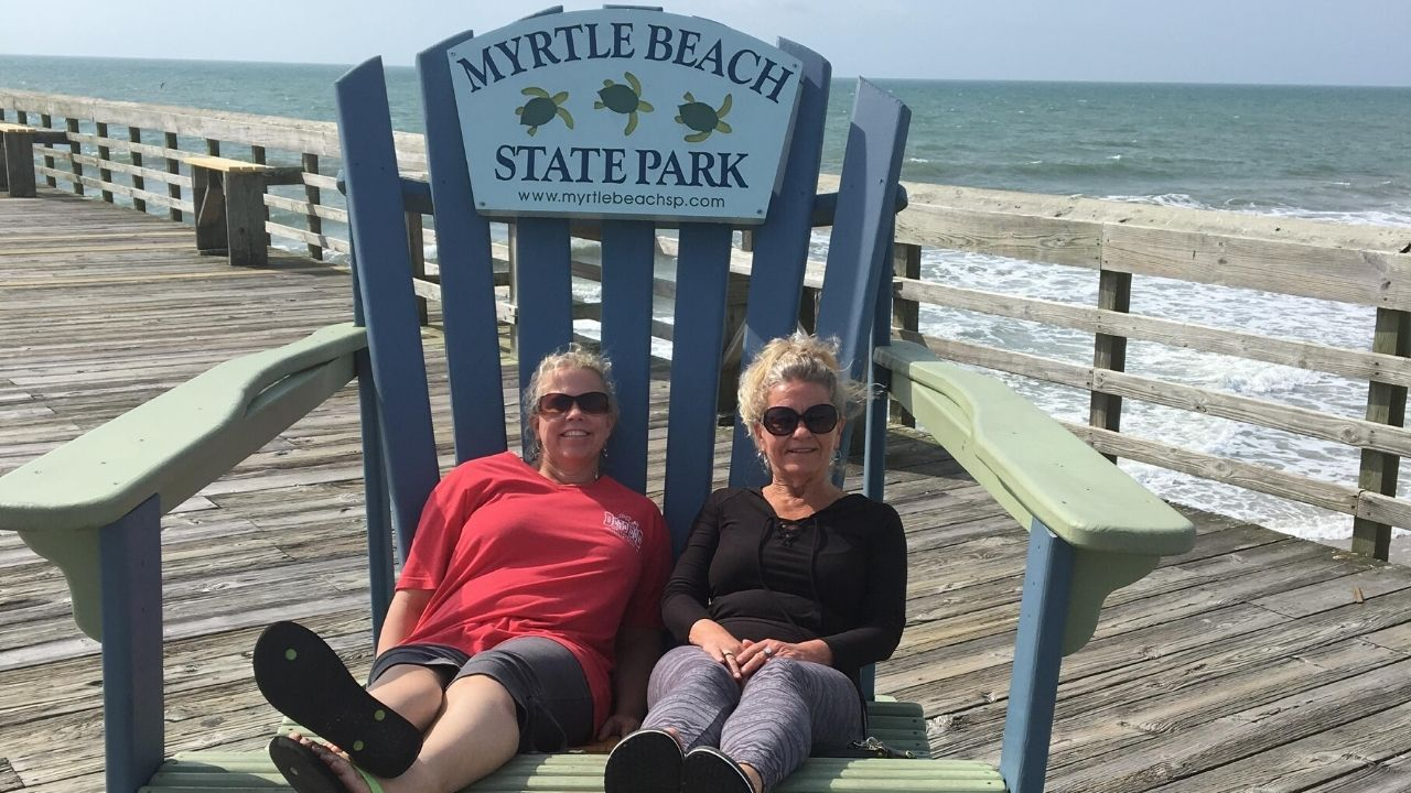 Two women sitting in a giant beach chair on a pier
