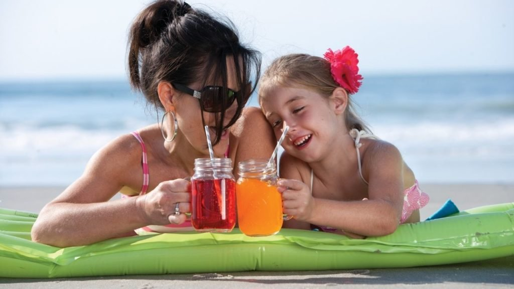 Mother and Daughter on Beach with Drinks